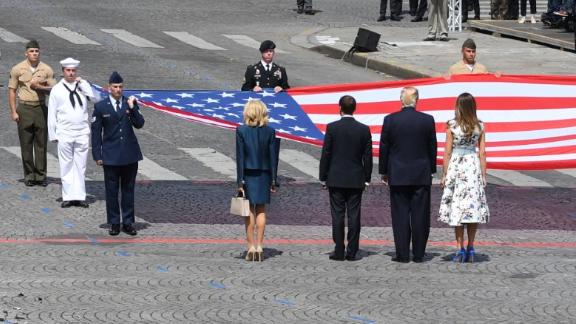 (RtoL) US First Lady Melania Trump, US President Donald Trump, French President Emmanuel Macron and his wife Brigitte Macron, walk towards the US national flag held by soldiers, as a French joint-army brass band performs, at the end of the annual Bastille Day military parade on the Champs-Elysees avenue in Paris on July 14, 2017.  