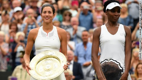 LONDON, ENGLAND - JULY 15:  Garbine Muguruza of Spain celebrates victory with the trophy alongside runner up Venus Williams of the United States after the Ladies Singles final on day twelve of the Wimbledon Lawn Tennis Championships at the All England Lawn Tennis and Croquet Club at Wimbledon on July 15, 2017, in London, England. (Photo by David Ramos/Getty Images)