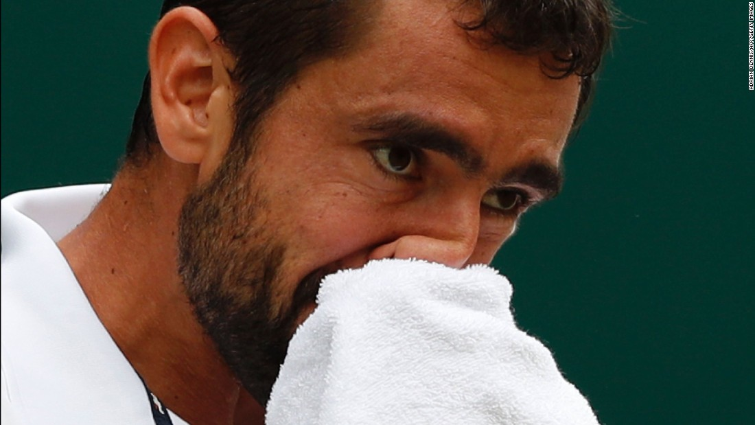 Cilic wipes his face with a towel during his match with Federer.