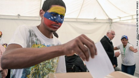 A Venezuelan residing in Colombia casts his vote during the symbolic vote.