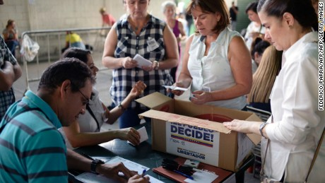 CORRECTION - Volunteers count the ballots during an opposition-organized vote to measure public support for Venezuelan President Nicolas Maduro's plan to rewrite the constitution in Caracas on July 16, 2017. Authorities have refused to greenlight the vote that has been presented as an act of civil disobedience and supporters of Maduro are boycotting it. Protests against Maduro since April 1 have brought thousands to the streets demanding elections, but has also left 95 people dead, according to an official toll.  / AFP PHOTO / FEDERICO PARRA / The erroneous mention[s] appearing in the metadata of this photo by FEDERICO PARRA has been modified in AFP systems in the following manner: [Volunteers count the ballots] instead of [People cast their ballots]. Please immediately remove the erroneous mention[s] from all your online services and delete it (them) from your servers. If you have been authorized by AFP to distribute it (them) to third parties, please ensure that the same actions are carried out by them. Failure to promptly comply with these instructions will entail liability on your part for any continued or post notification usage. Therefore we thank you very much for all your attention and prompt action. We are sorry for the inconvenience this notification may cause and remain at your disposal for any further information you may require.        (Photo credit should read FEDERICO PARRA/AFP/Getty Images)