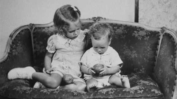 McCain sits on a sofa with his sister, Sandy, in a reproduction of a family photo taken around 1938. McCain was born in 1936 to Roberta McCain and John McCain Jr., a Navy admiral.