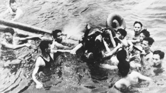 During the Vietnam War, McCain's plane was shot down and captured by North Vietnamese forces. Here, he is pulled out of a lake in Hanoi by North Vietnamese soldiers and civilians in October 1967. McCain broke both arms and his right knee upon ejection and lost consciousness until he hit the water. Upon capture, McCain was beaten, he has said. He was held for five years by the North Vietnamese and tortured.