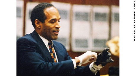 O.J. Simpson tries on a leather glove allegedly used in the killings of Nicole Brown Simpson and Ronald Goldman during testimony in Simpson's murder trial on June 15, 1995, in Los Angeles.