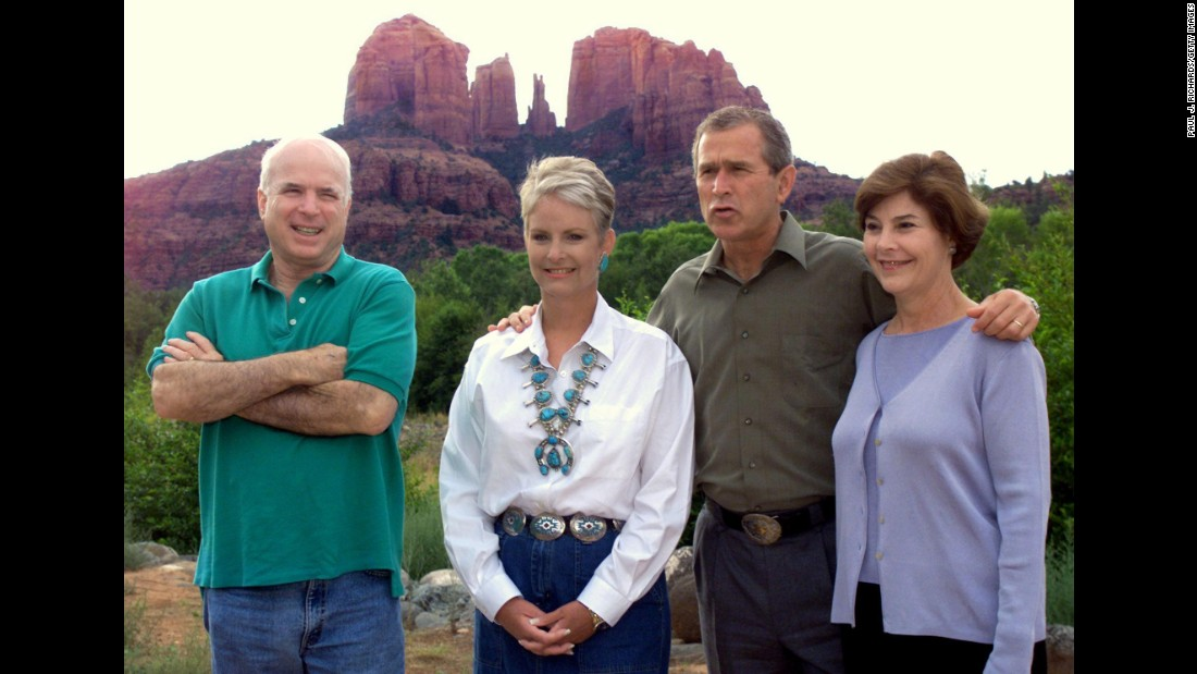 Republican presidential nominee George W. Bush and his wife, Laura, pose with hosts John and Cindy McCain on August 13, 2000, at Arizona's Red Rock Crossing as Cathedral Rock looms in the background.