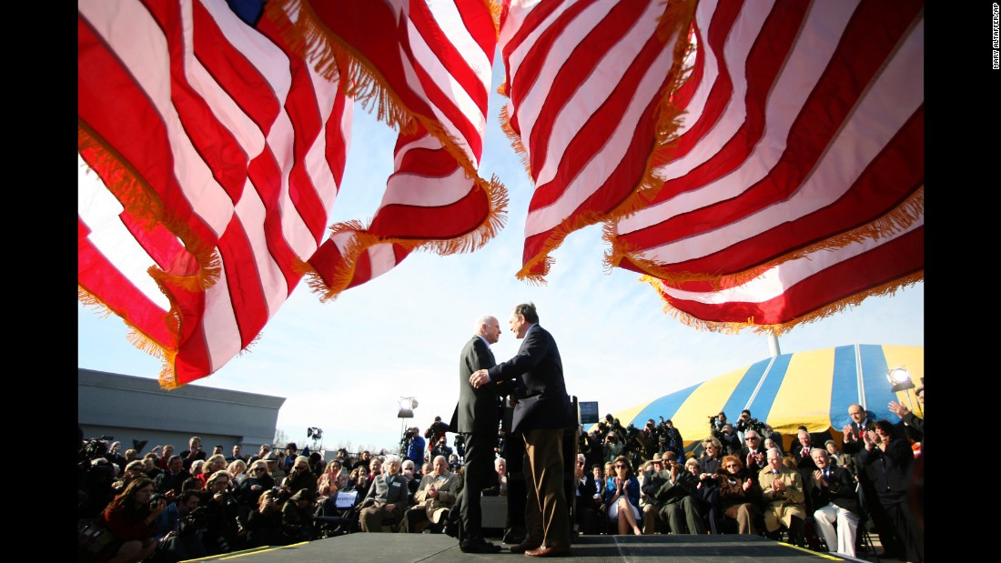 "McCain, left, is introduced by retired Rear Adm. Tom Lynch before delivering a speech on April 2, 2008, at the Navy-Marine Corps Stadium in Annapolis, Maryland, during his ""Service to America"" tour."