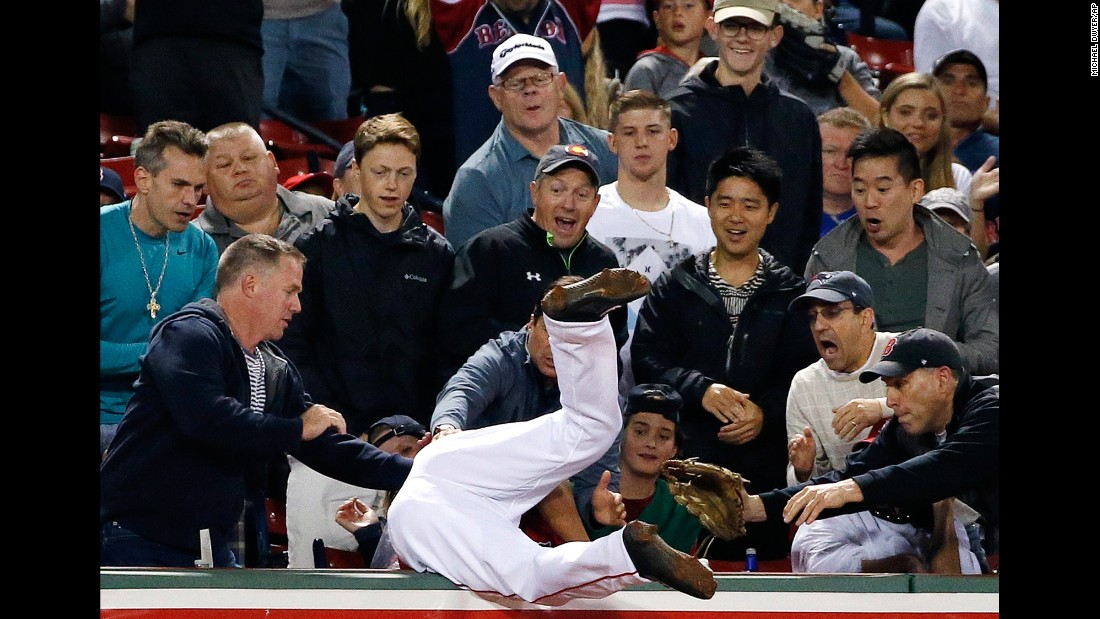Boston Red Sox's Tzu-Wei Lin flips over into the stands after catching the pop foul by New York Yankees' Jacoby Ellsbury during the ninth inning in Boston on Friday, July 14.