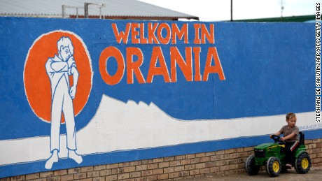 "A young South African Afrikaner boy plays by a painted wall reading ""Welcome in Orania"" in Afrikaans."