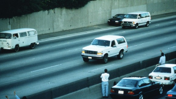 In footage seen on TV screens around the world, police chase a white Ford Bronco with a fugitive Simpson inside on the Los Angeles freeways on June 17, 1994. The Bronco eventually returned to Simpson's home in the Brentwood section of Los Angeles, and he surrendered to police on murder charges in the deaths of his ex-wife and Ronald Goldman.