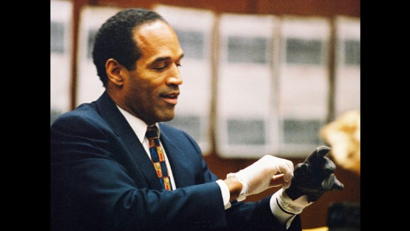 """""""If it doesn't fit, you must acquit"""" was defense attorney Cochran's mantra during the trial. Here, Simpson tries on a leather glove tied to the crime scene at his murder trial on June 15, 1995."""