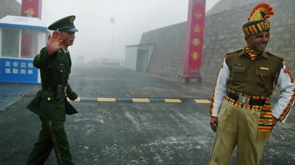 A Chinese soldier (L) and an Indian soldier stand guard at the Chinese side of the ancient Nathu La border crossing between India and China, 2008.