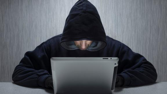 An anonymous hooded male using a tablet computer to represent a cyber criminal. (Photo by: Loop Images/UIG via Getty Images)