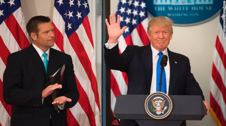 President Donald Trump waves after speaking alongside then-Kansas Secretary of State Kris Kobach during the first meeting of the Presidential Advisory Commission on Election Integrity in the Eisenhower Executive Office Building next to the White House in Washington, DC, in July 2017.