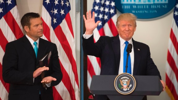 US President Donald Trump waves after speaking alongside Kansas Secretary of State Kris Kobach (L) during the first meeting of the Presidential Advisory Commission on Election Integrity in the Eisenhower Executive Office Building next to the White House in Washington, DC, July 19, 2017. / AFP PHOTO / SAUL LOEB        (Photo credit should read SAUL LOEB/AFP/Getty Images)