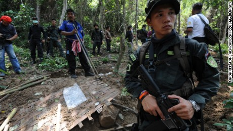Soldiers stand guard as rescue workers and forensic officials dig out skeletons from shallow graves covered by bamboo at the site of a mass grave at an abandoned jungle camp in the Sadao district of Thailand's southern Songkhla province bordering Malaysia on May 2, 2015. The badly decayed remains of at least three more migrants thought to be from Myanmar or Bangladesh were exhumed on May 2 from a mass grave in southern Thailand, as details emerged of the maltreatment endured at the remote people smugglers' camp. Authorities have found the remains of at least eight people since the grim discovery of the site on May 1, a find which has again laid bare Thailand's central role in a regional human trafficking trade.  AFP PHOTO / Madaree TOHLALA        (Photo credit should read MADAREE TOHLALA/AFP/Getty Images)