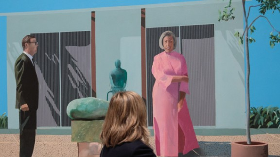 """Visitors view """"American Collectors (Fred and Marcia Weisman)"""" by David Hockney."""