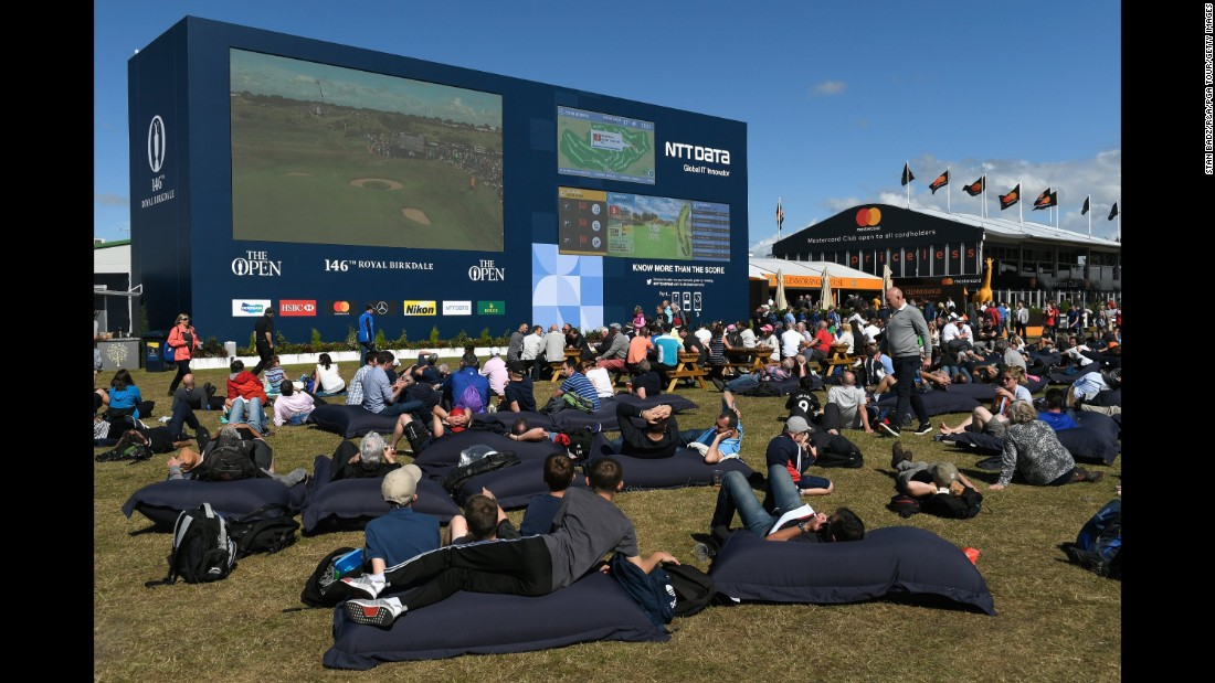Golf fans on giant beanbags watch the action on a big screen in the spectator village.