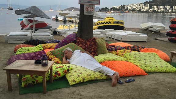 A man in Bitez, a resort town west of Bodrum in Turkey sleeps on the beachfront following the earthquake in the early hours of Friday morning.