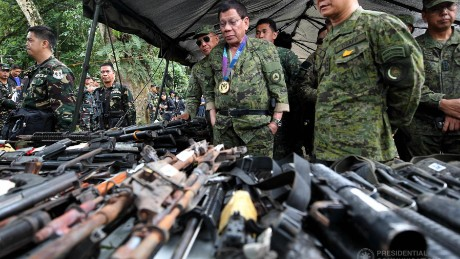 Philippines President Rodrigo Duterte examines captured militant weaponry at Camp Ranao, Marawi, while visiting troops fighting ISIS-aligned militants holed up in the city.