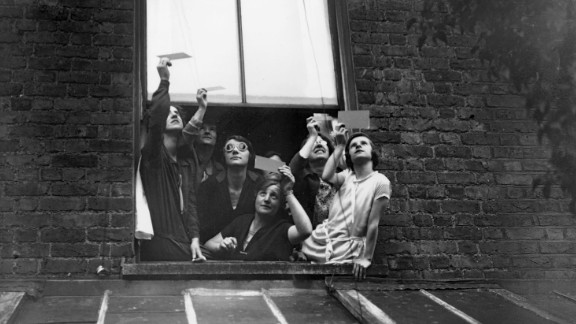 A group gathered in a window to view the total solar eclipse over London through smoked glass. 29th June 1927