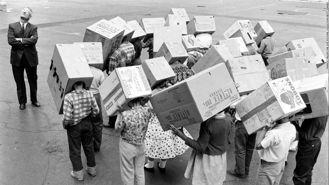 "5th grade students from Emerson Elementary School with ""sunscopes"" (cardboard boxes) over their heads, used to view a solar eclipse without harming their eyes in Maywood, Illinois, 1963."