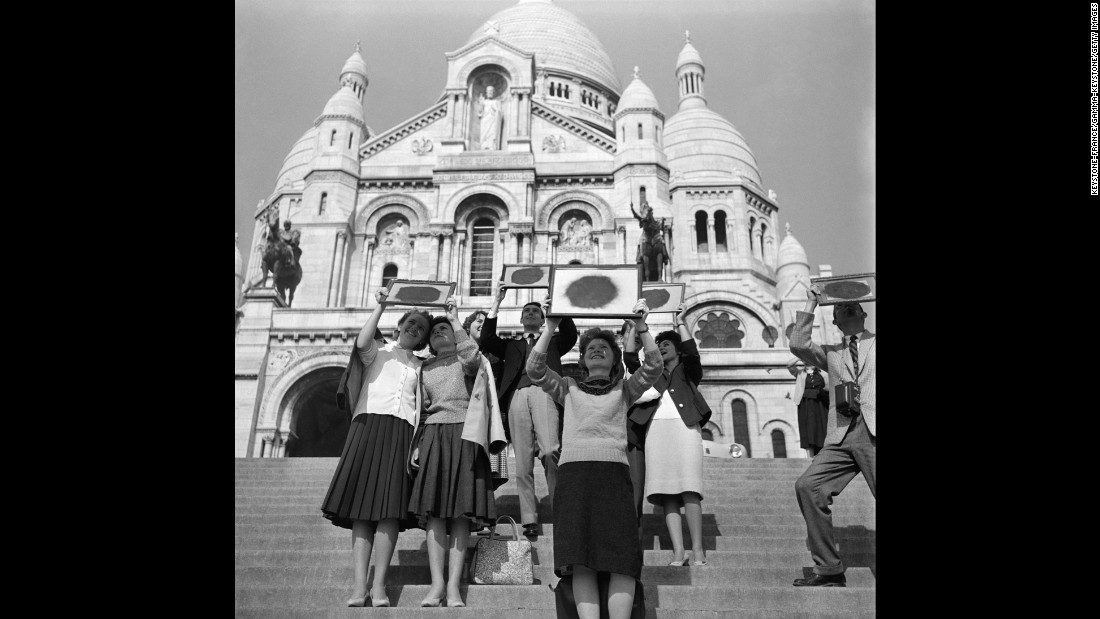 Parisians watching the solar eclipse with the help of smoked glass on the steps of Sacre-Coeur, Paris, France, in October 1959.