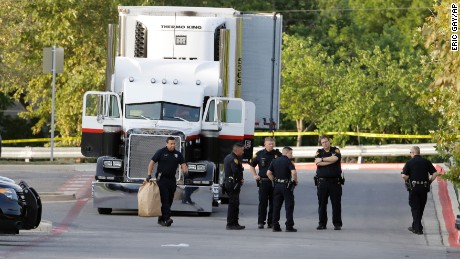 San Antonio officers investigate the scene where people were found dead in a tractor-trailer outside a Walmart.