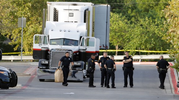 San Antonio officers investigate the scene where people were found dead in the parked truck.