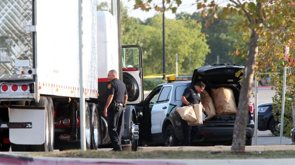 Authorities investigate a semi-truck where people were found dead Sunday.