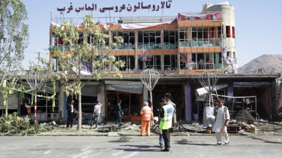 Municipality workers cleans up in front of a wedding hall at the site of a suicide attack in Kabul, Afghanistan, Monday, July 24, 2017. A suicide car bomb killed dozens of people as well as the bomber early Monday morning in a western neighborhood of Afghanistan's capital where several prominent politicians reside, a government official said. (AP Photos/Massoud Hossaini)