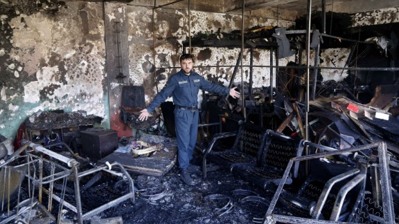 An Afghan security official inspects the scene of the bombing on Monday.