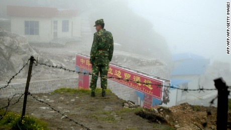 In this photograph taken on July 10, 2008, a Chinese soldier stands guard on the Chinese side of the ancient Nathu La border crossing between India and China. When the two Asian giants opened the 4,500-metre-high (15,000 feet) pass in 2006 to improve ties dogged by a bitter war in 1962 that saw the route closed for 44 years, many on both sides hoped it would boost trade. Two years on, optimism has given way to despair as the flow of traders has shrunk to a trickle because of red tape, poor facilities and sub-standard roads in India's remote northeastern mountainous state of Sikkim. AFP PHOTO/Diptendu DUTTA (Photo credit should read DIPTENDU DUTTA/AFP/Getty Images)