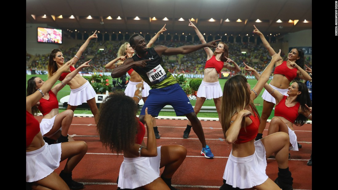 Usain Bolt, the world's fastest man, strikes his signature pose with cheerleaders after winning the 100-meter race at the Diamond League meet in Monaco on Friday, July 21.
