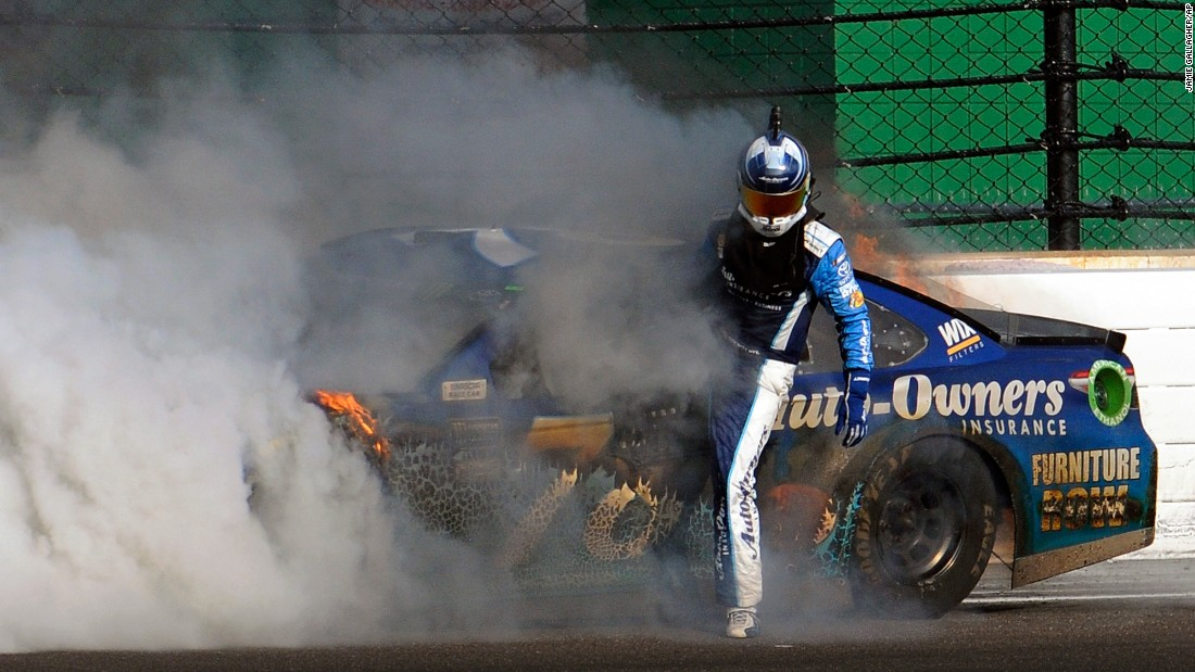 Martin Truex Jr. climbs out of his car after crashing with Kyle Busch at the Brickyard 400 on Sunday, July 23. Despite not finishing the race, Truex still leads the standings in NASCAR's top circuit.
