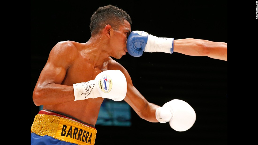 Robert Barrera eats a punch from Ryoichi Taguchi during their light-flyweight bout in Tokyo on Sunday, July 23. Taguchi defended his WBA title with a ninth-round stoppage.