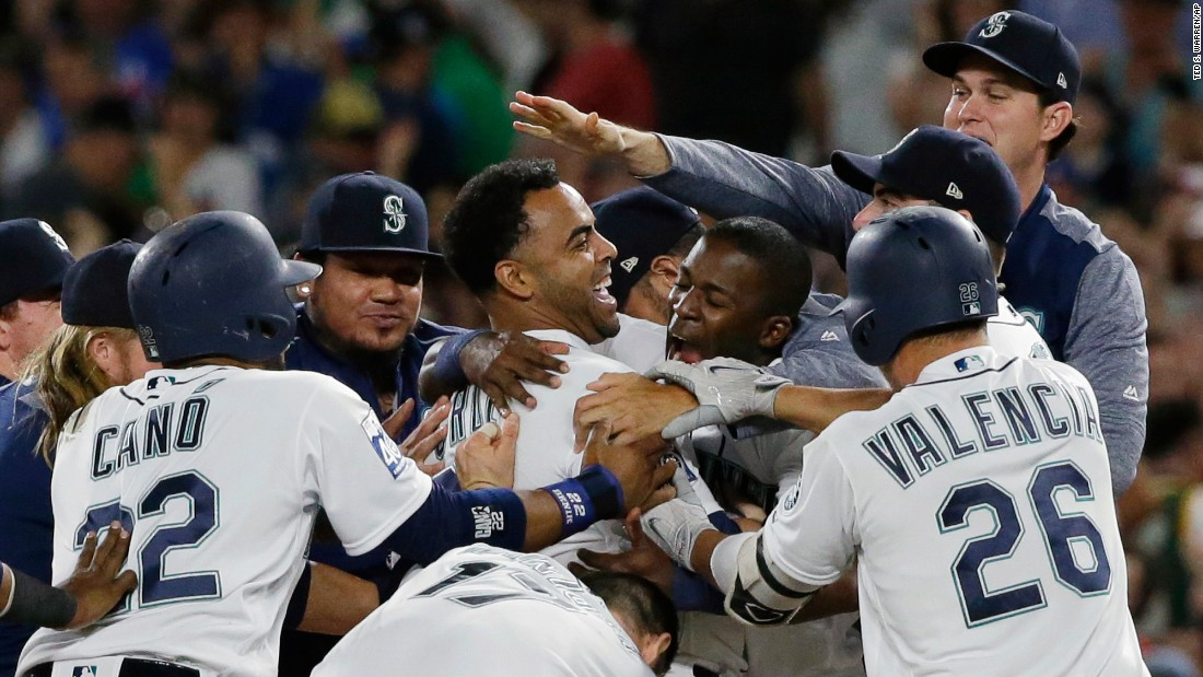 Nelson Cruz is mobbed by his Seattle teammates after his base hit beat the New York Yankees on Saturday, July 22.