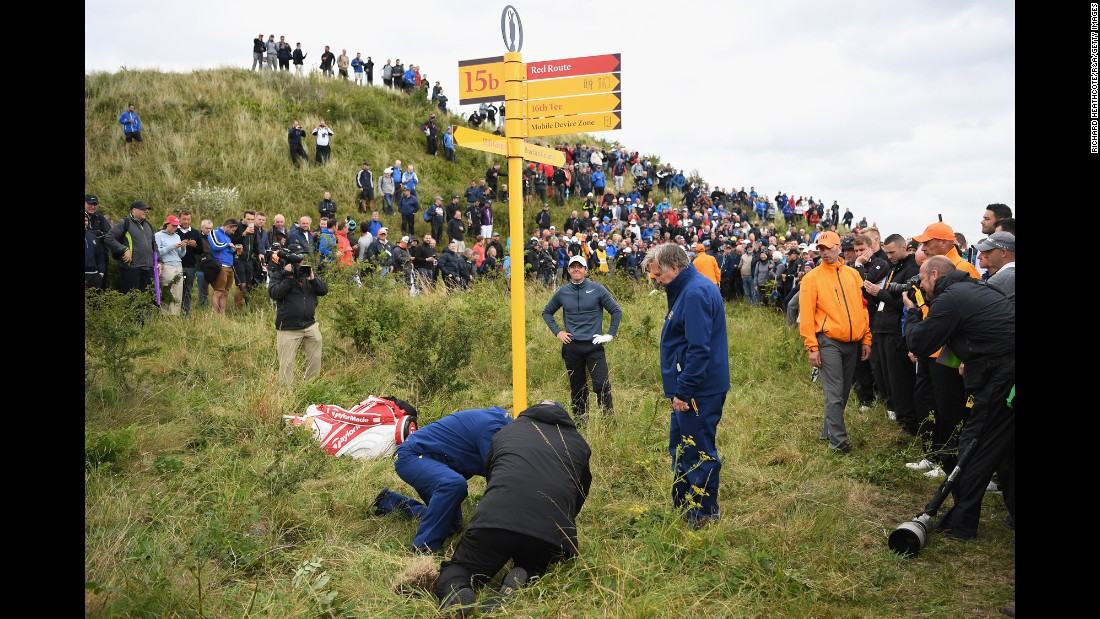 "Officials remove a sign at the Royal Birkdale Golf Club so that Rory McIlroy, hands on hips, could play a shot at the Open Championship on Friday, July 21. McIlroy's ball was embedded in the ground, so he was unable to take a free drop to avoid the sign. <a href=""http://www.cnn.com/2017/07/17/sport/gallery/what-a-shot-sports-0717/index.html"" target=""_blank"">See 27 amazing sports photos from last week</a>"