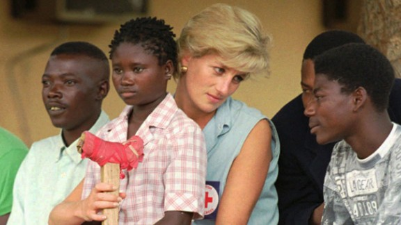 Diana talks to amputees in Angola, where she traveled in January 1997 to bring attention to the anti-land mine campaign of the International Red Cross. Sitting on her lap is Sandra Thijica, a 13-year-old who lost her left leg to a land mine.