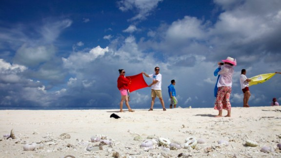 Chinese tourists pose with the country's flag as they visit the Parcael Islands.
