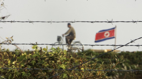 """DANDONG, LIAONING, CHINA - OCTOBER 18:  A North Korean man riding a bicycle near a North Korean flag is seen through the newly installed fence by the Chinese side in this picture taken on October 18, 2006 in the Chinese border city of Dandong, Liaoning Province of China. China urged North Korea not to escalate international tensions, after Pyongyang said the UN resolution imposing sanctions over its nuclear weapons test was a """"declaration of war.""""  (Photo by Cancan Chu/Getty Images)"""