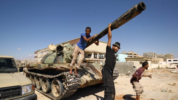 Members of Haftar's army pose with a tank in the city of Benghazi in July.