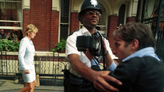 A police officer holds back a photographer as Diana walks by in July 1996. It had just been announced that Diana and Charles had divorced.