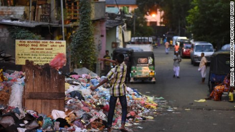 A Sri Lankan man throws trash onto garbage piled on a street in Colombo on June 26, 2017.