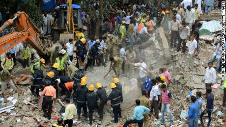 Indian rescue workers look for survivors in debris at the site of a building collapse in Mumbai on July 25, 2017.