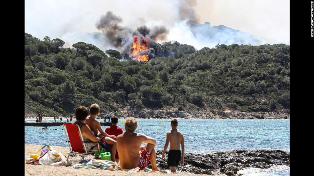 People watch a wildfire burn near a beach in La Croix-Valmer, France, on Tuesday, July 25.