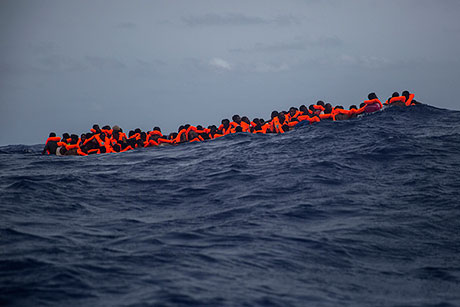 Migrants from sub-Saharan Africa wait for a rescue boat after at least 13 migrants died during the journey in July.