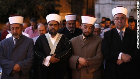 Sheikh Omar Kiswani (2-L), Al-Aqsa director, and other clergymen join as Palestinian Muslim worshippers pray outside Jerusalem's Old City.