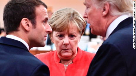 TOPSHOT - (L-R) French President Emmanuel Macron, German Chancellor Angela Merkel and US President Donald Trump confer at the start of the first working session of the G20 meeting in Hamburg, northern Germany, on July 7. Leaders of the world's top economies will gather from July 7 to 8, 2017 in Germany for likely the stormiest G20 summit in years, with disagreements ranging from wars to climate change and global trade. / AFP PHOTO / AFP PHOTO AND POOL / John MACDOUGALL        (Photo credit should read JOHN MACDOUGALL/AFP/Getty Images)