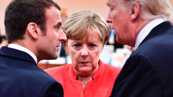 TOPSHOT - (L-R) French President Emmanuel Macron, German Chancellor Angela Merkel and US President Donald Trump confer at the start of the first working session of the G20 meeting in Hamburg, northern Germany, on July 7. Leaders of the world