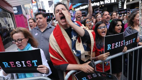 "Dozens of protesters gather in Times Square near a military recruitment center to show their anger at President Donald Trump's decision to reinstate a ban on transgender individuals from serving in the military on July 26, 2017 in New York City. Trump citied the ""tremendous medical costs and disruption"" for his decision."
